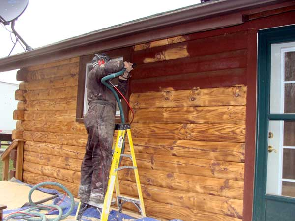 Paint removal in process from log home